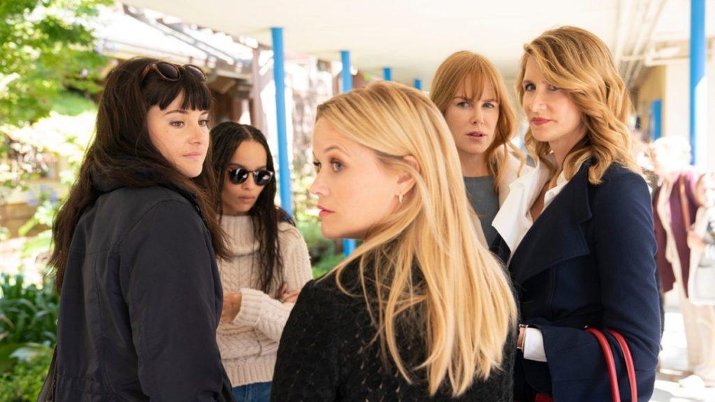 Imagem da segunda temporada de Big Little Lies (HBO). Jane (Shailene Woodley), Bonnie (Zoë Kravitz), Madeline (Reese Whiterspoon), Celeste (Nicole Kidman) e Renata (Laura Dern) reúnem-se em uma roda, em um amplo e ensolarado corredor. Renata e Madeline observam algo atrás desta última.
