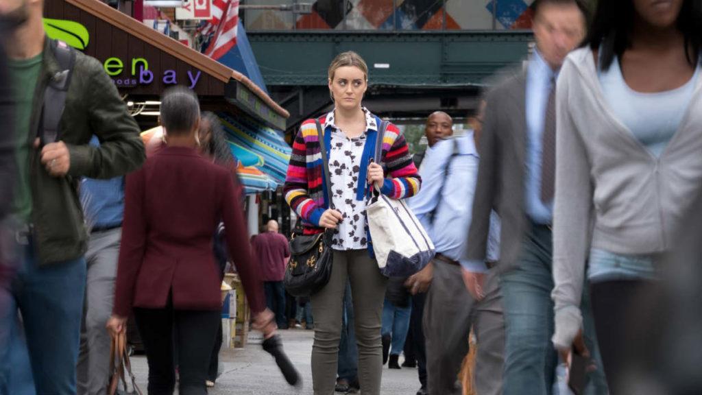 Imagem da última temporada de Orange Is the New Black. Piper (Taylor Schilling) anda no meio de uma multidão, já em liberdade, com expressão desconfiada.