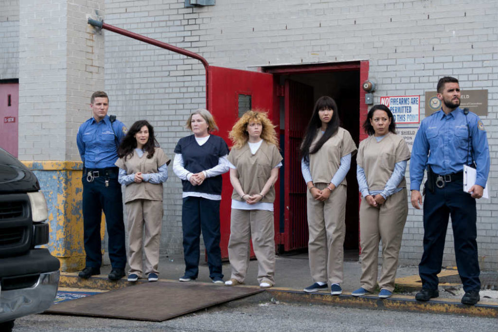Imagem da última temporada de Orange Is the New Black. Algumas das personagens principais aguardam, algemadas, a chegada de alguém, na área externa de Litchfield.