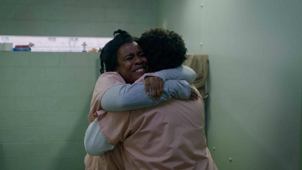 Imagem da última temporada de Orange Is the New Black. Suzanne (Uzo Aduba) abraça a amiga Cindy (Adrienne C. Moore), dentro de uma cela da cadeia.