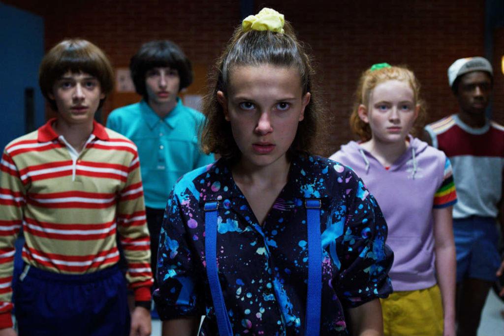 Nesta imagem de Stranger Things 3, Will, Mike, Eleven, Max e Lucas olhem em direção à câmera, com expressões de seriedade. Todos usam roupas coloridas, típicas dos anos 1980.