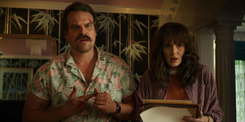 Nesta imagem de Stranger Things 3, Hopper e Joyce olham em direção à câmera, com expressões de incredulidade. Joyce segura papéis nas mãos. Hopper usa uma camisa florida, verde e rosa.