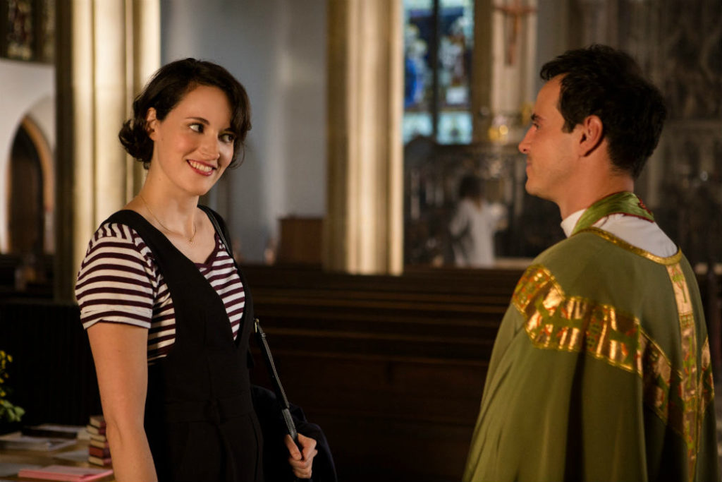 Cena da segunda temporada de Fleabag. A protagonista (Phoebe Waller-Bridge) encara sorridente o padre (Andrew Scott) por quem se apaixona. De batina, o padre sorri de volta para ela. Ambos estão no interior de uma igreja.