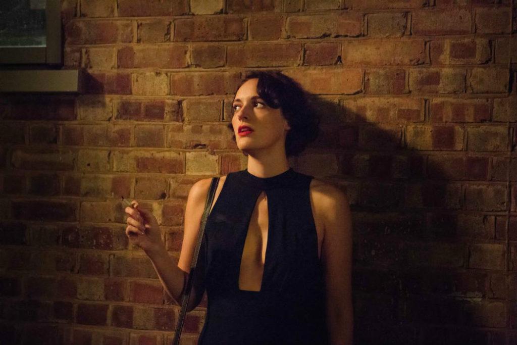 Cena da segunda temporada de Fleabag. A protagonista (Phoebe Waller-Bridge) está encostada em uma parede de tijolos. Ela fuma um cigarro e olha para a sua direita, de modo desconfiado. A personagem usa um vestido preto muito decotado e elegante.